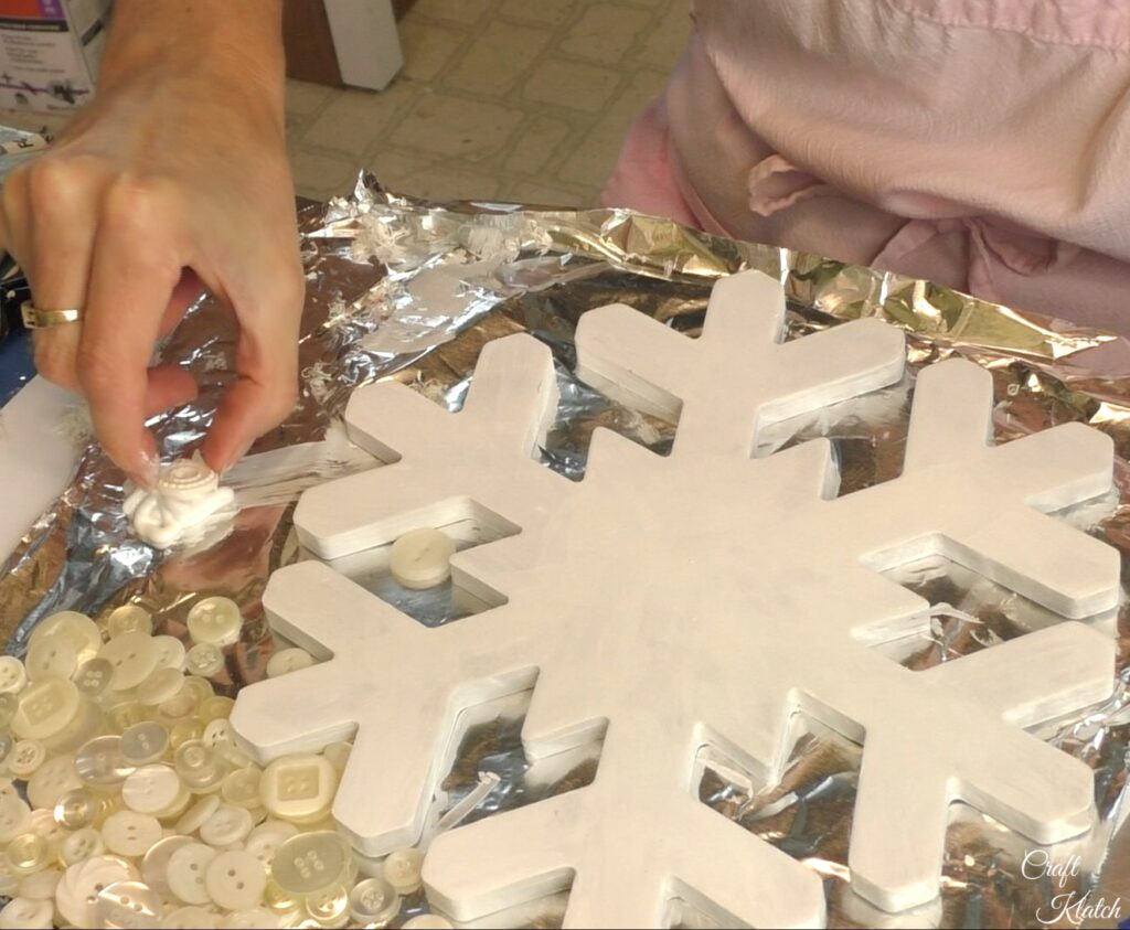 Dip white button into the glue for the snowflake decoration