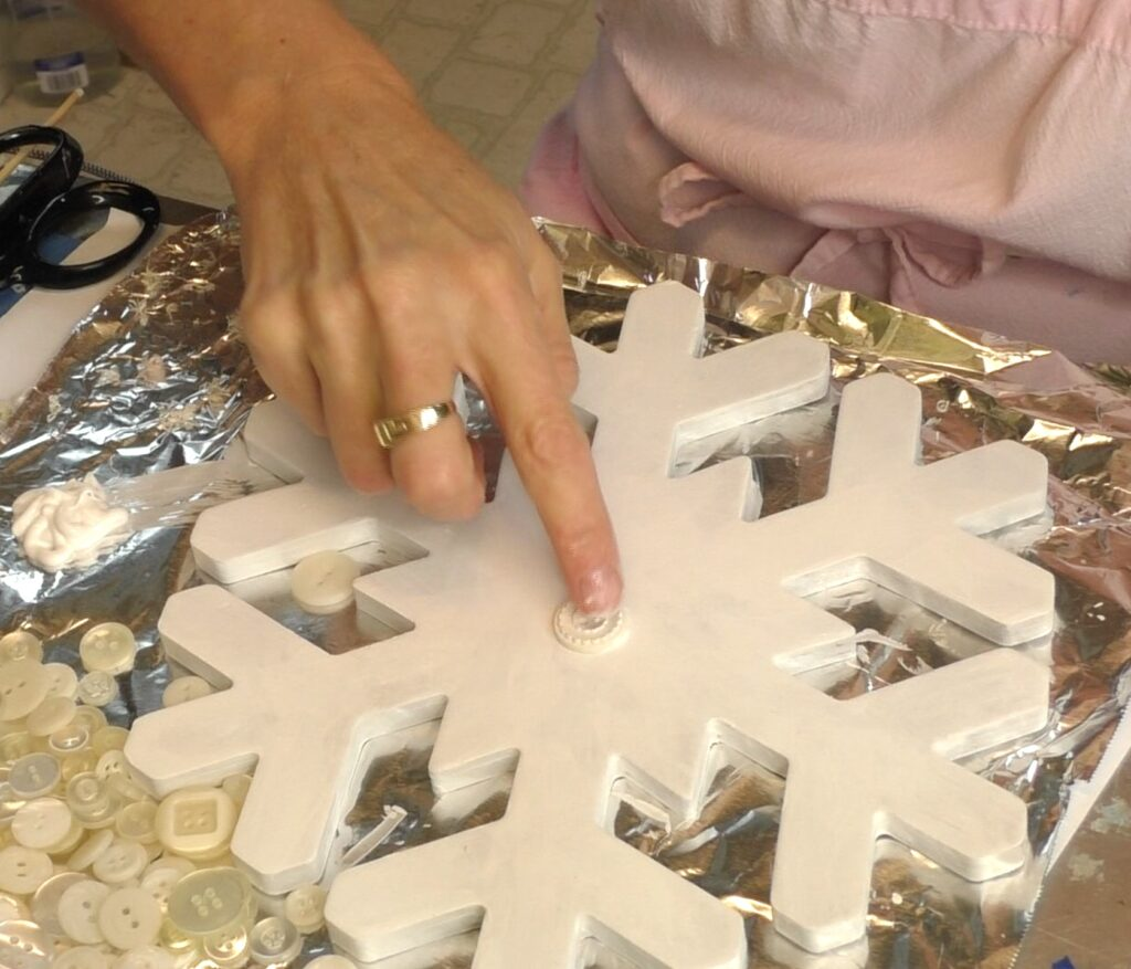 Glue button into middle of snowflake craft