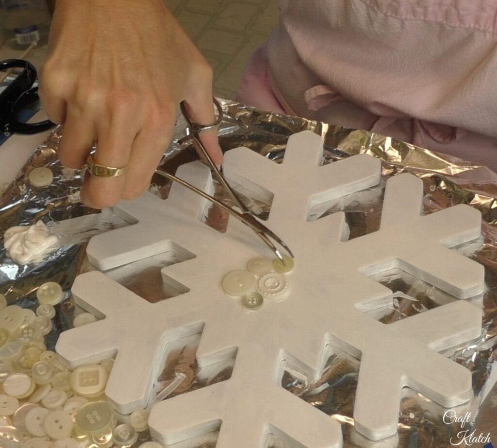 Keep dipping and adding buttons to snowflake craft