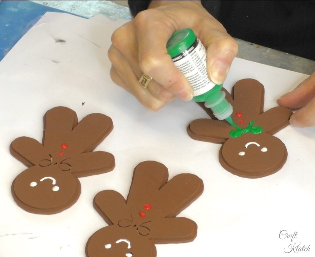 Decorate gingerbread men with green fabric paint