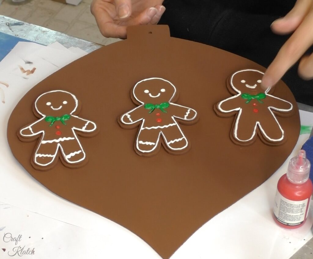 Three gingerbread men on brown Christmas ornament