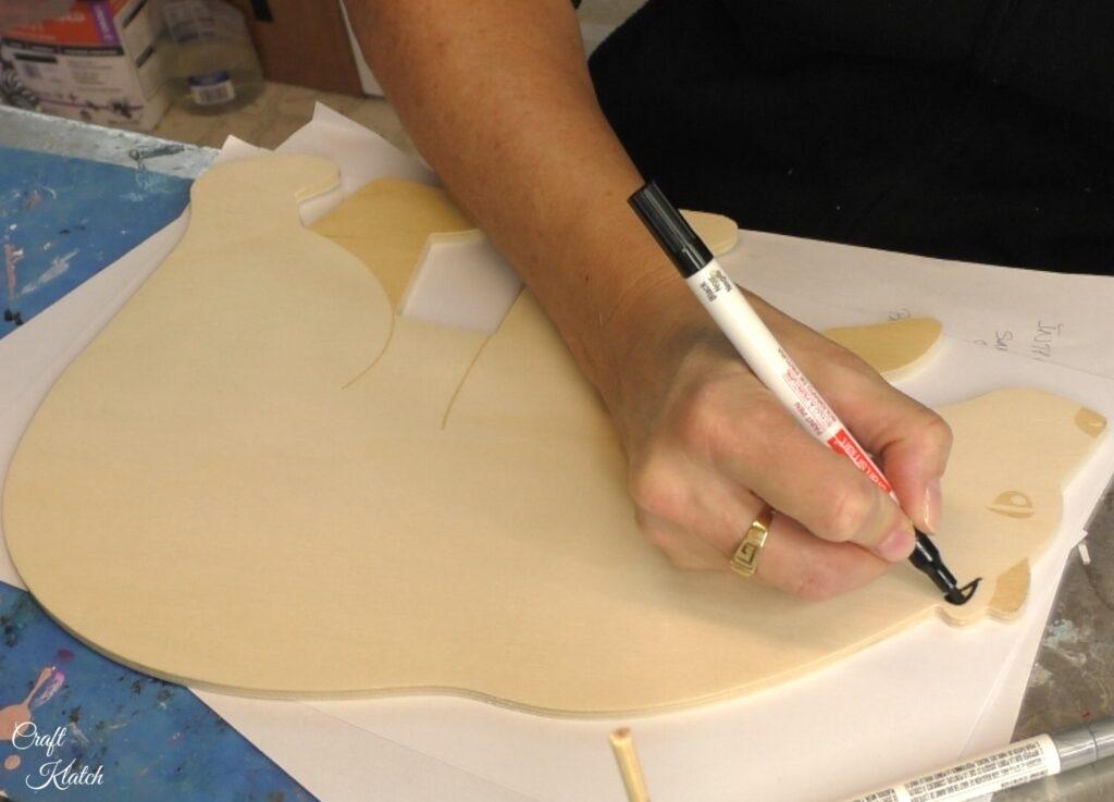 Use black paint marker to darken features