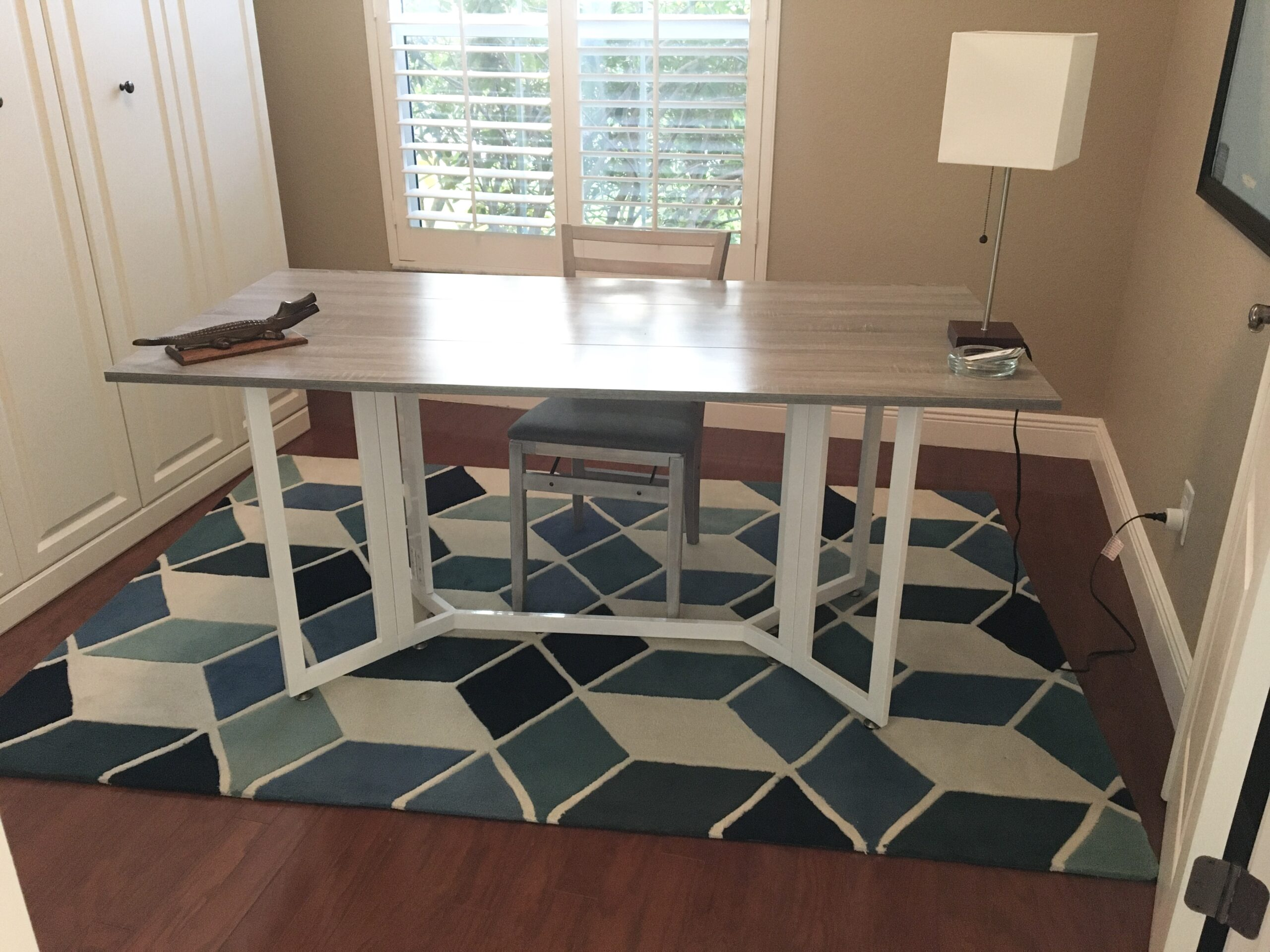 Folding gray top table with white legs used as a desk in home office.