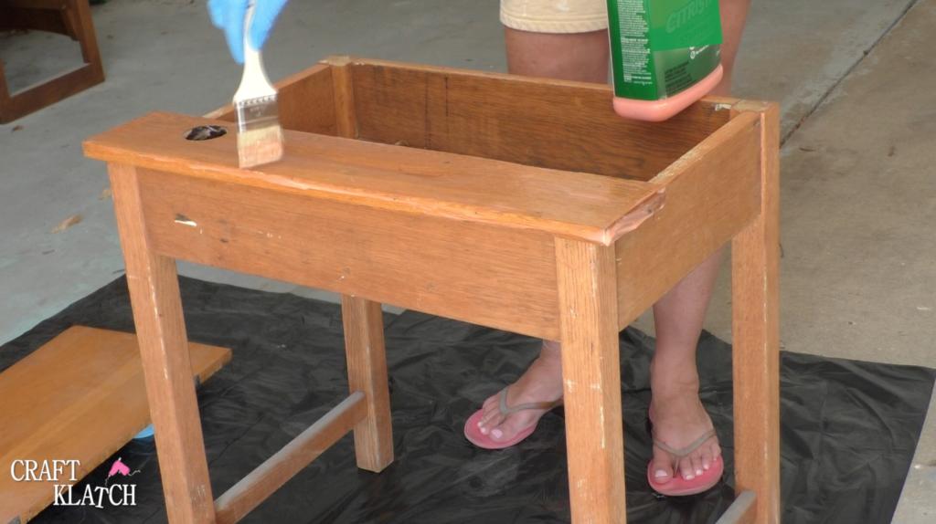 Brushing Citristrip stripper on an old desk