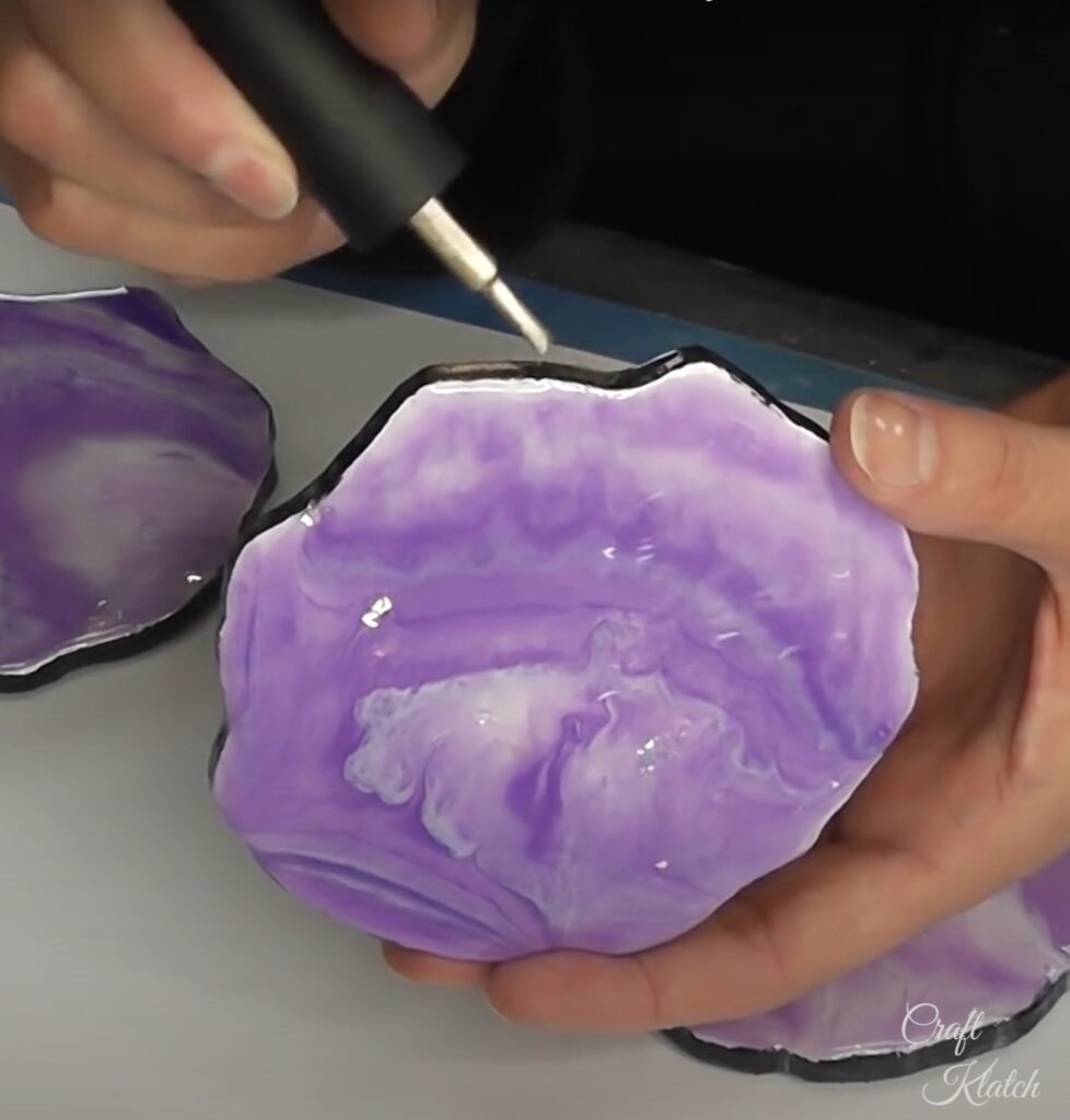 Painting gold nail polish on edge of purple and white resin geode coasters