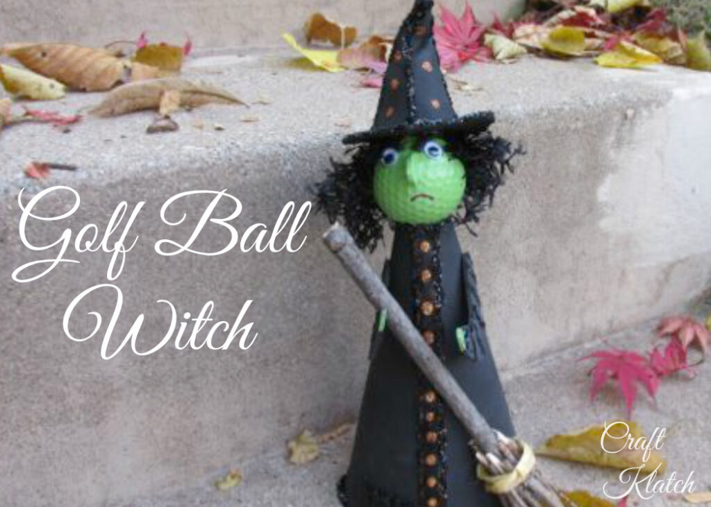 Green golf ball witch with black dress and hat and witch hat holding broom