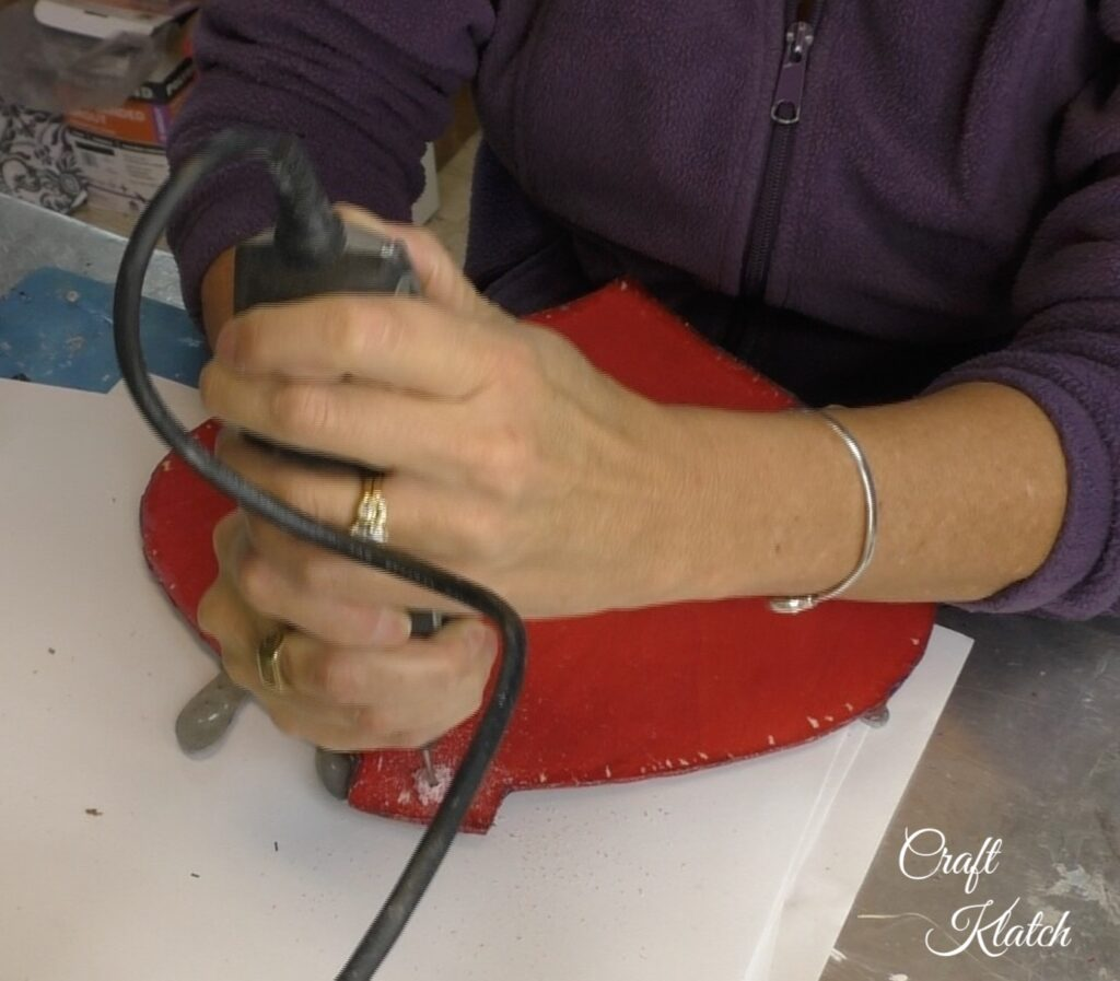 Drilling hole into red Dollar Tree ornament