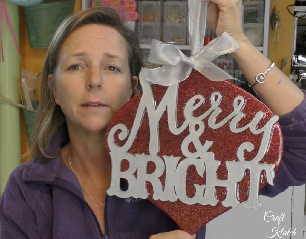 Mona of Craft Klatch holding up finished Dollar Tree ornament makeover Merry and Bright