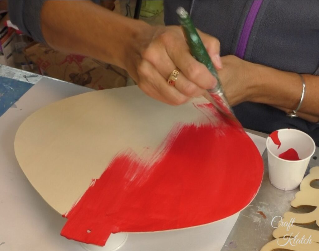 Unfinished Dollar Tree ornament being painted red