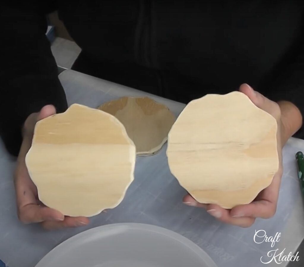 Hands holding two unfinished wood rounds