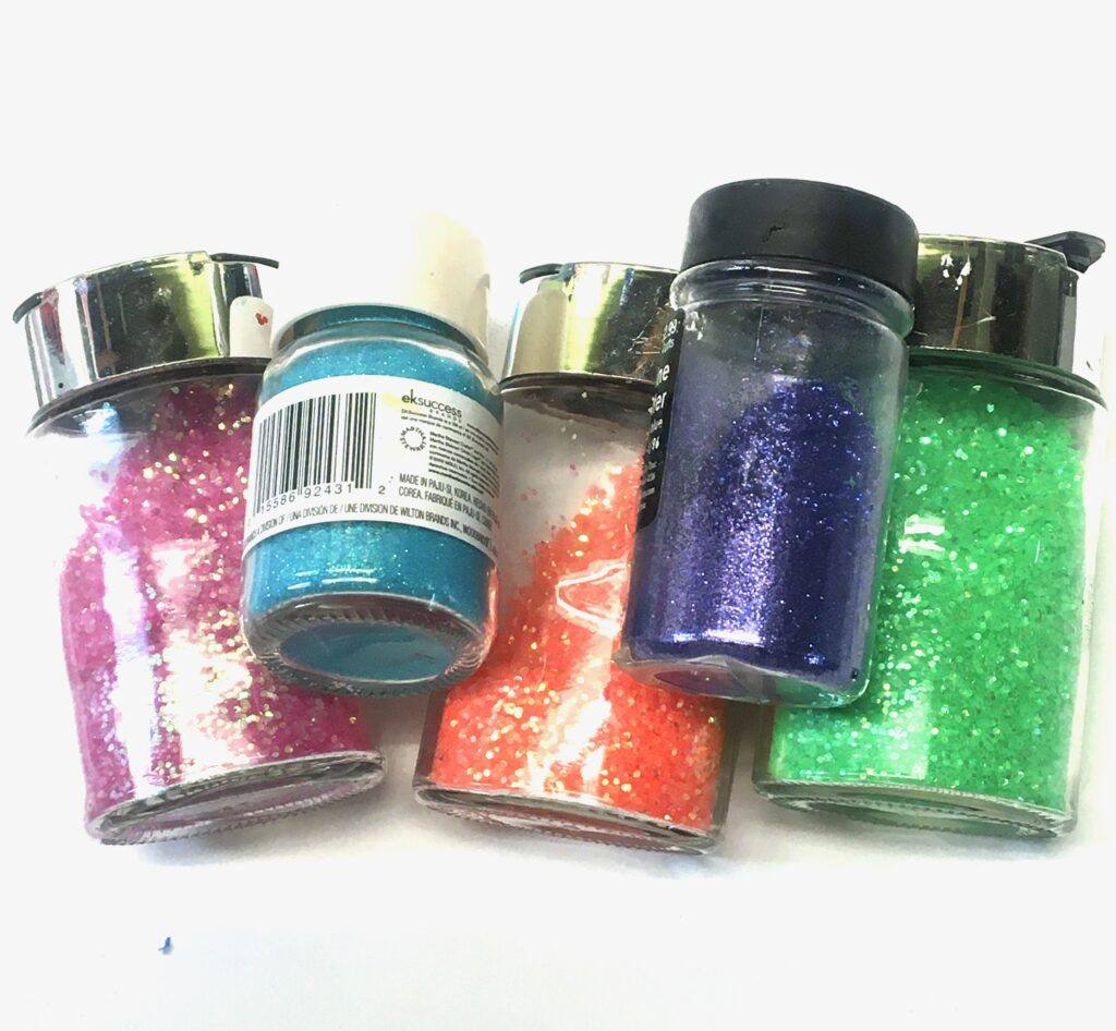 Jars of pink, blue orange and green glitter
