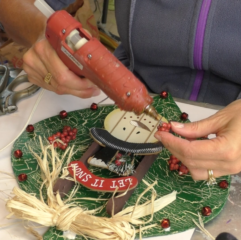 Gluing red berries onto ornament