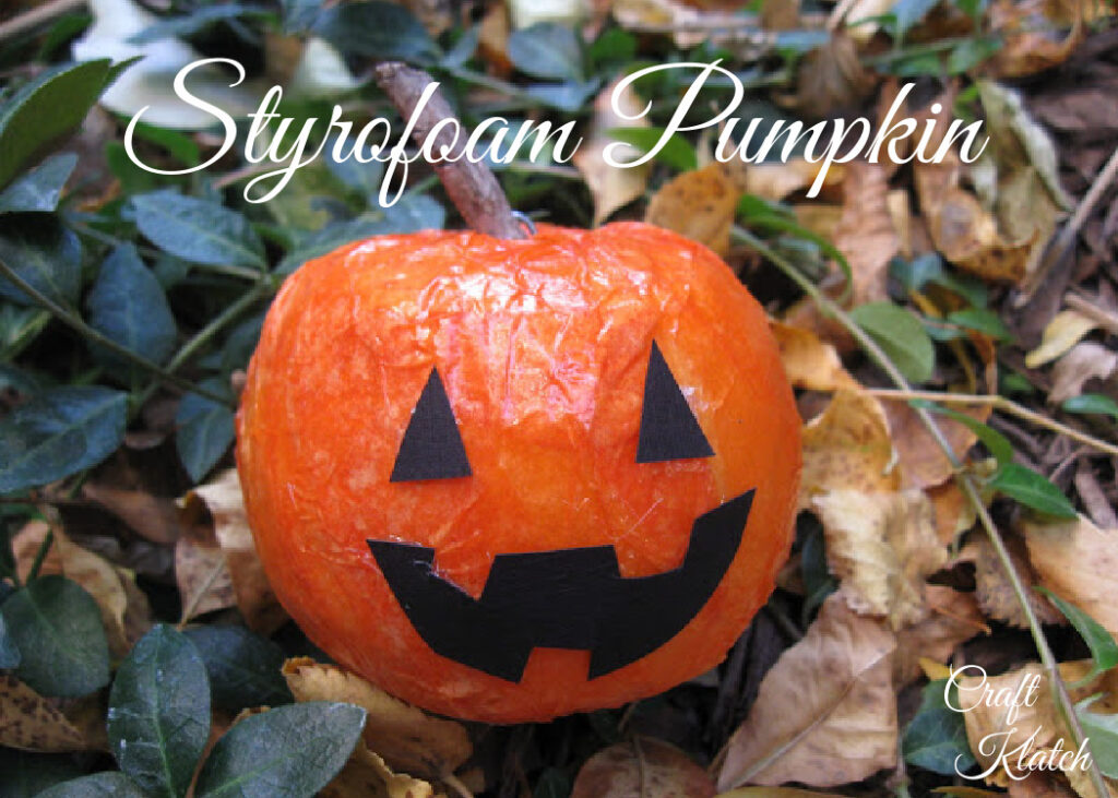 Styrofoam pumpkin with black triangle eyes and mouth with a wood stick stem