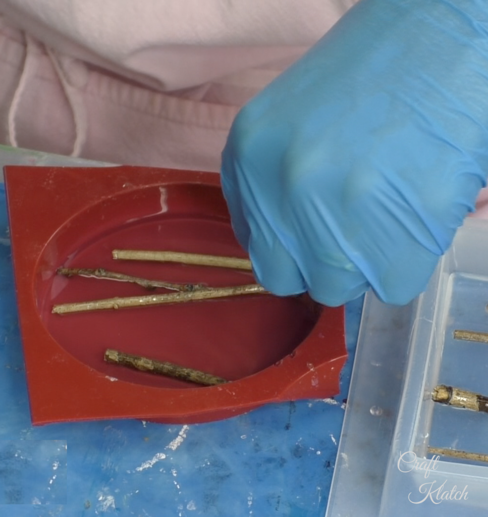 Laying twigs in resin in a round red silicone coaster mold