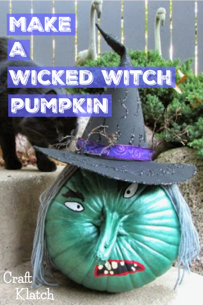 Green wicked witch painted pumpkin with gray hair and black witch hat and stem for nose fall crafts for kids