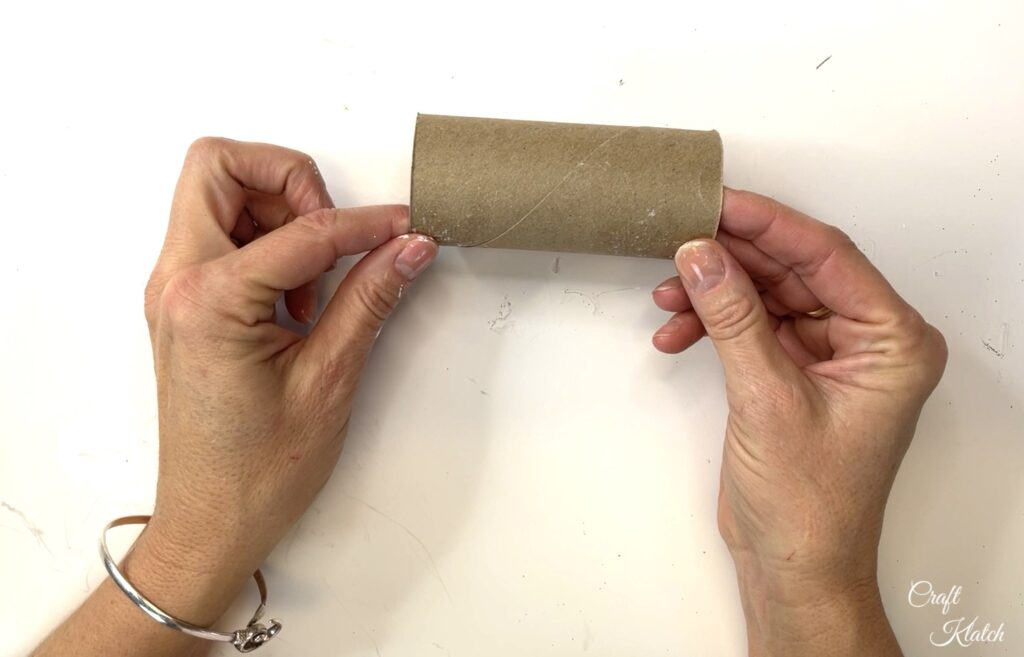 Holding empty toilet paper roll to make a Christmas ornament
