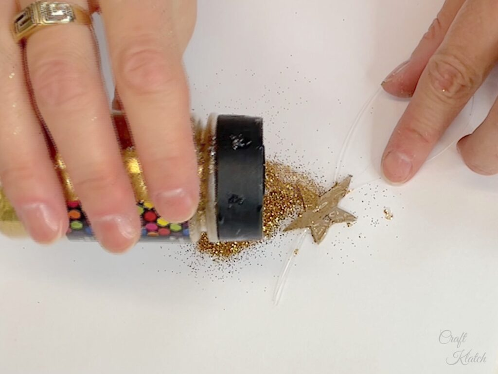 Glue fishing line between two stars and add glitter