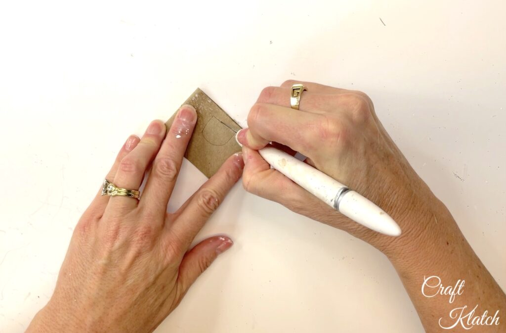 Use craft knife to cut an opening out of toilet paper roll