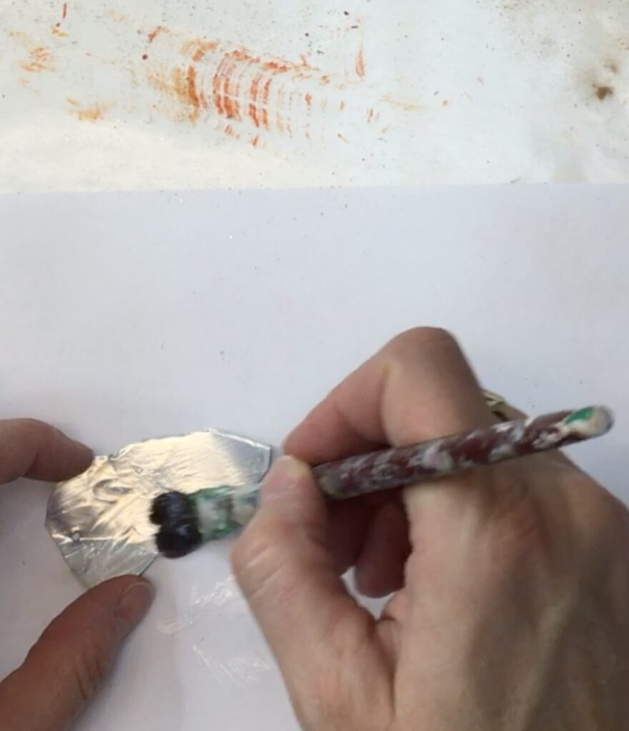 Brushing Mod Podge on metal leaf