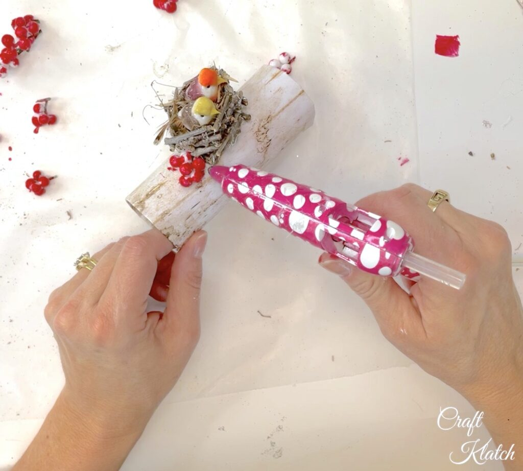 Hot glue red berries to the bird Christmas tree ornament