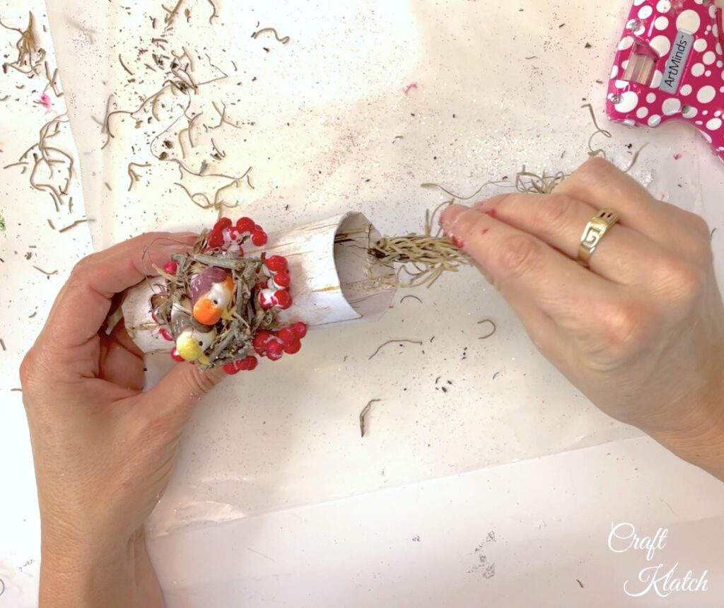 Hot glue spanish moss into the sides of the bird Christmas tree ornament diy