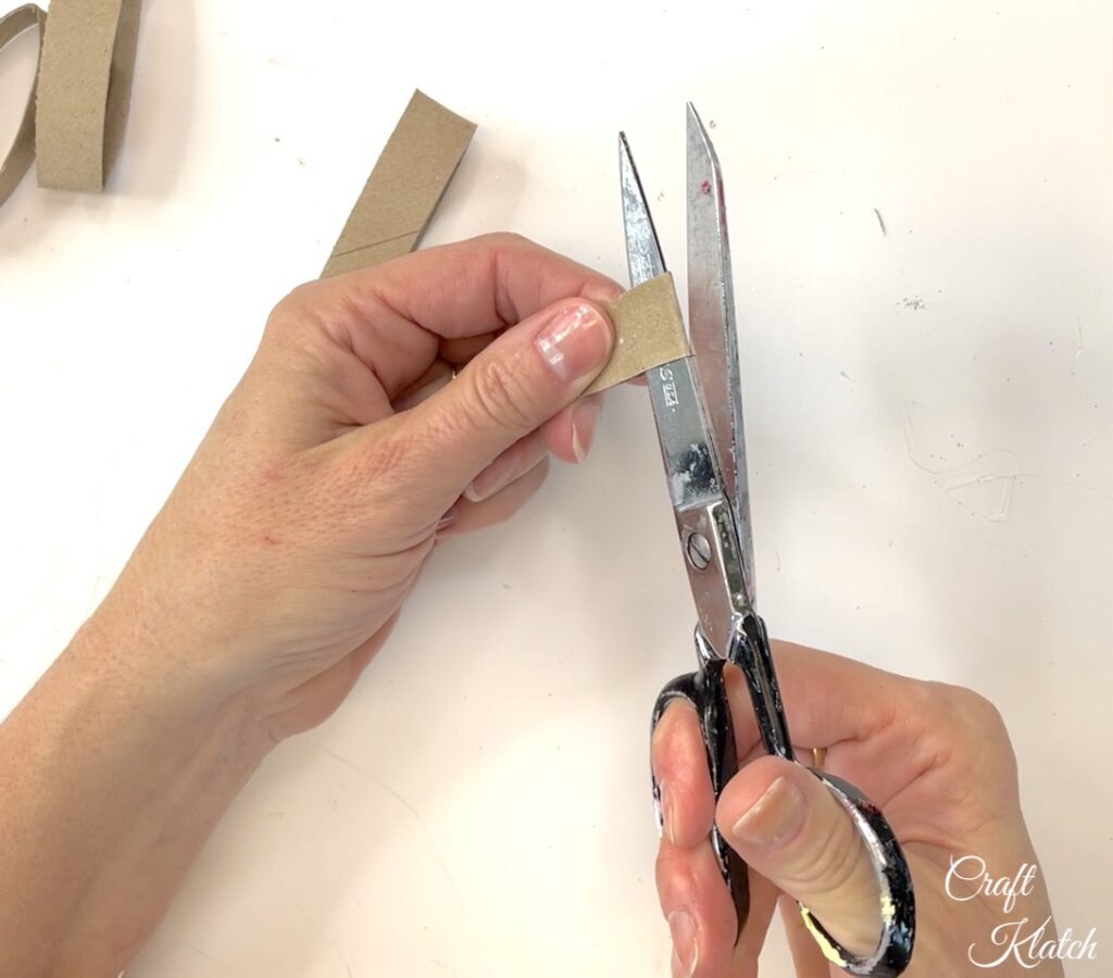 Cut open one end of toilet paper roll strips
