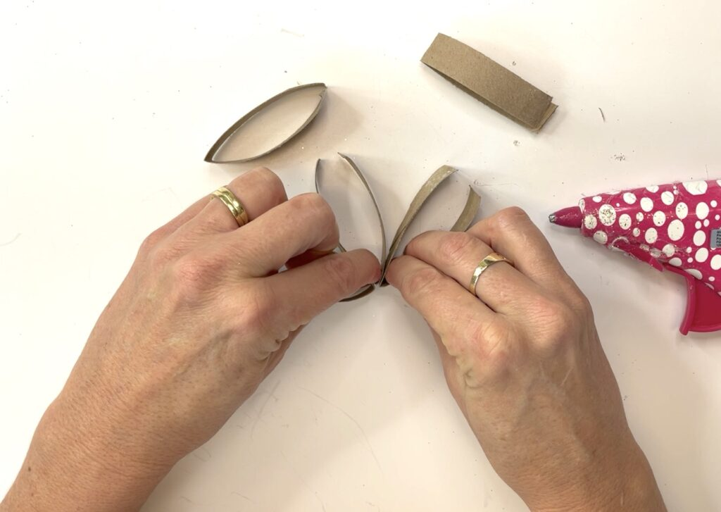 Hold toilet paper roll pieces together while hot glue cools