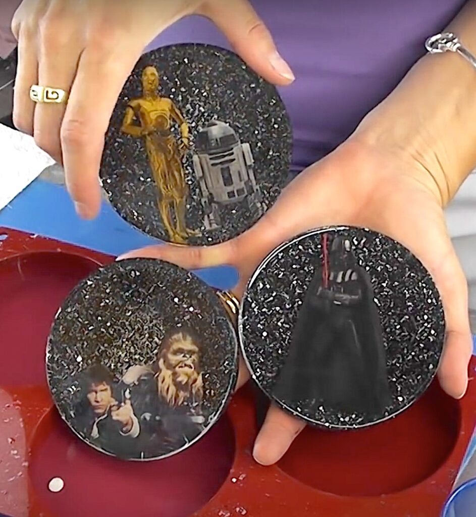 Star Wars project   Three Star Wars coasters with black glitter backgrounds. One with Darth Vader. One with Han Solo, Chewbacca and Yoda. One with R2 D2 and C3PO.